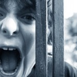 Picture of boy yelling to be heard through a fence